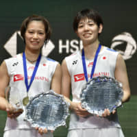 Yuki Fukushima (left) and Sayaka Hirota stand on the podium after winning the women's doubles title at the All England Open on Sunday. | AP