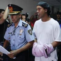 Ronaldinho talks as he walks while being escorted by police officers with his hands handcuffed in Asuncion, Paraguay, on Saturday. | AP