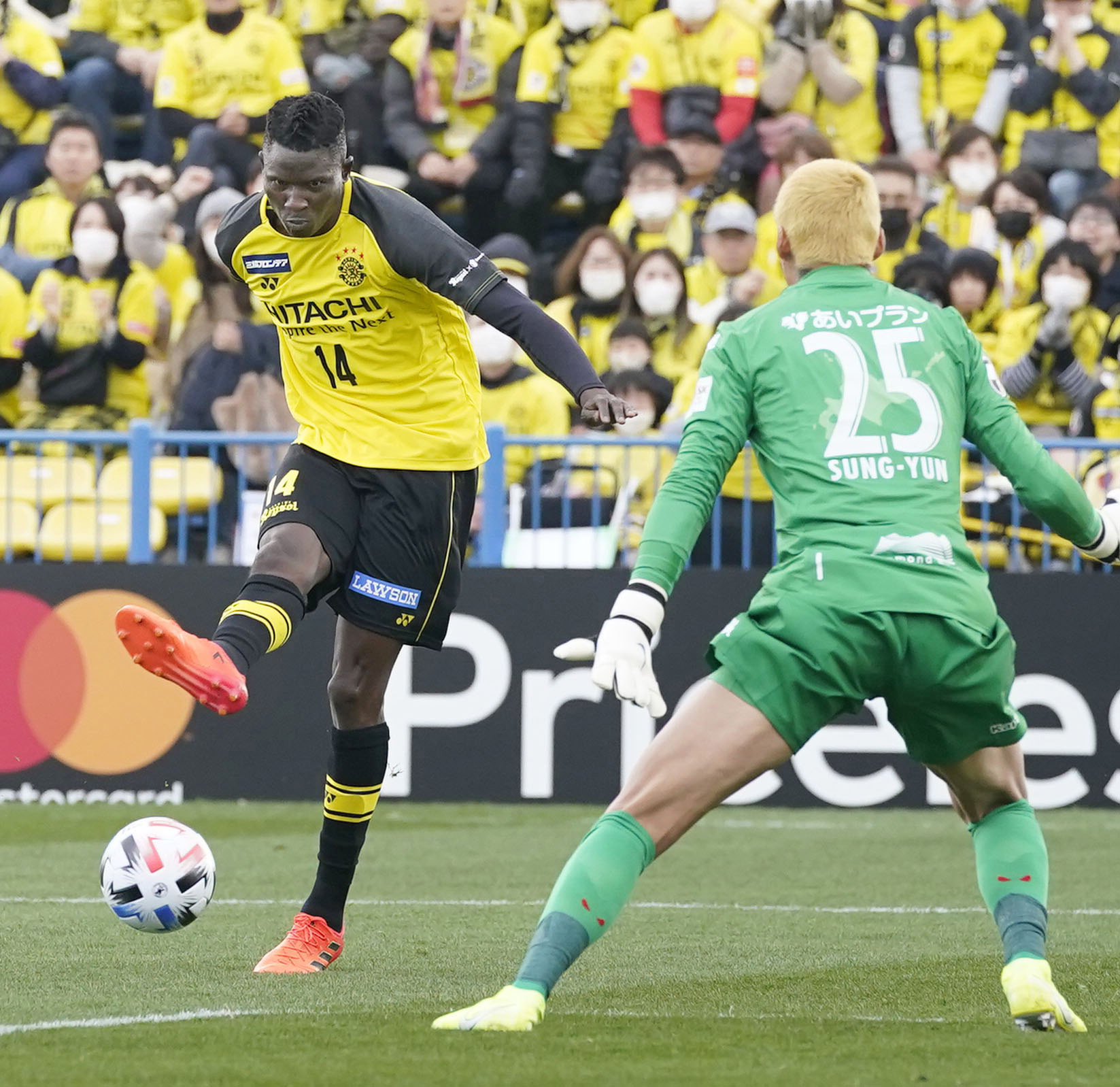 Reyosl striker Michael Olunga (left) scores against Consadole goalkeeper Gu Sung-yun in the first half of their J. League opening-round game on Feb. 22 in Kashiwa, Chiba Prefecture. | KYODO