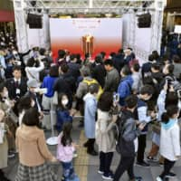 Spectators wearing face masks wait to see the Olympic flame on Saturday in Sendai. | KYODO