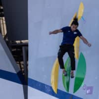 A Tokyo 2020 organizing staff member jumps after climbing a wall during a bouldering test on Friday at Aomi Urban Sports Park. | AFP-JIJI