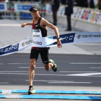 Suguro Osako sets a national record as he crosses the finish line on Sunday. | AFP-JIJI