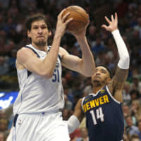 The Mavericks' Boban Marjanovic takes the ball inside as the Nuggets' Gary Harris defends in the second half on Wednesday in Dallas. | AP