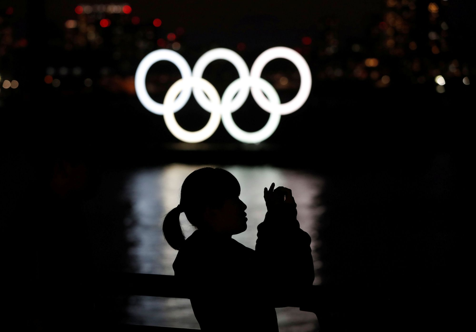 A woman takes a photograph in front of the giant Olympic rings at Odaiba Marine Park in Tokyo on Sunday. | REUTERS