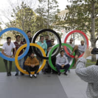 A group of students from Uruguay pose for a souvenir picture on the Olympic Rings set outside the Olympic Stadium in Tokyo on Saturday. | AP