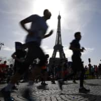 Runners pass the Eiffel Tower during the 42nd edition of the Paris Marathon on April 8, 2018. | AFP-JIJI