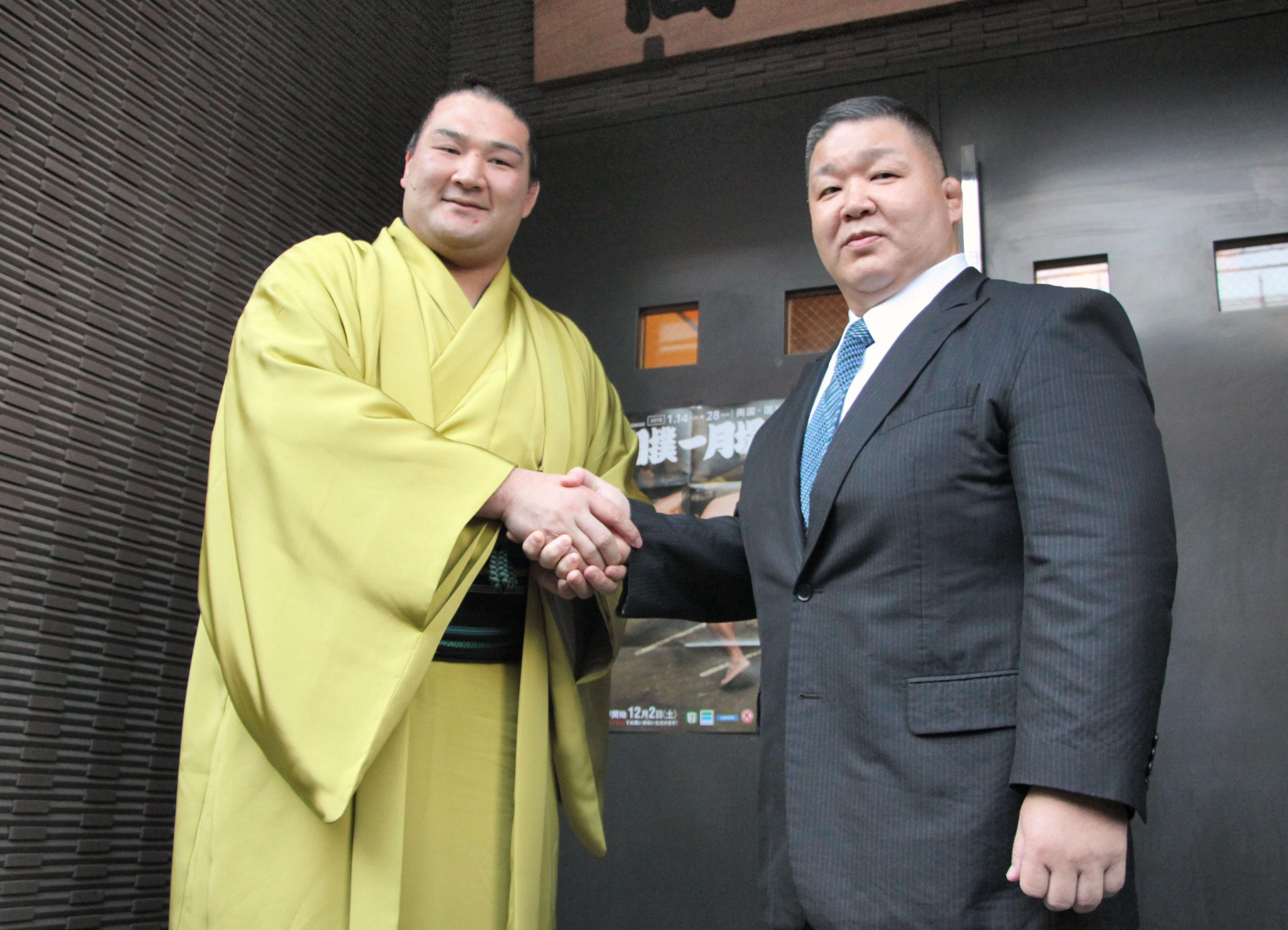 Former makuuchi wrestler Akinoshima (right), now known as Takadagawa stablemaster, shakes hands with Ryuden on Dec. 26, 2017, in Koto Ward. | KYODO