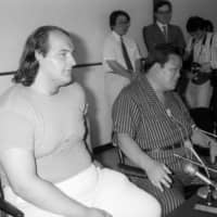 Kototenzan (left) speaks to the media alongside Sadogatake stablemaster (father of the current Sadogatake) before the Nagoya Basho in 1986. He retired from sumo before the start of the tournament. | KYODO