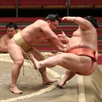 Ishiura (left) drives Chirotairyu out of the ring by his mawashi (belt) during Day 4 of the Spring Grand Sumo Tournament at Edion Arena Osaka on Wednesday.   NIKKAN SPORTS
