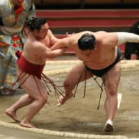No. 4 maegashira Enho (left) grabs the arm of second-ranked maegashira Okinoumi and forces him out of the raised ring on the fifth day of the Spring Grand Sumo Tournament at Edion Arena Osaka on Thursday. | NIKKAN SPORTS
