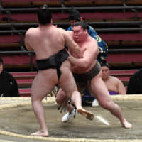 Yokozuna Hakuho (right) shoves Ryuden during their bout on the ninth day of the Spring Grand Sumo Tournament on Monday in Osaka. | NIKKAN SPORTS