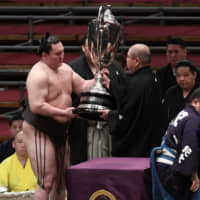 Yokozuna Hakuho receives the Emperor's Cup from JSA chairman Hakkaku after clinching his 44th championship by defeating Kakuryu on the final day of the Spring Grand Sumo Tournament at Edion Arena Osaka on Sunday. | NIKKAN SPORTS