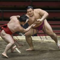 Asanoyama (right) wrestles Enho during Day 10 of the Spring Grand Sumo Tournament on March 17 in Osaka. | KYODO