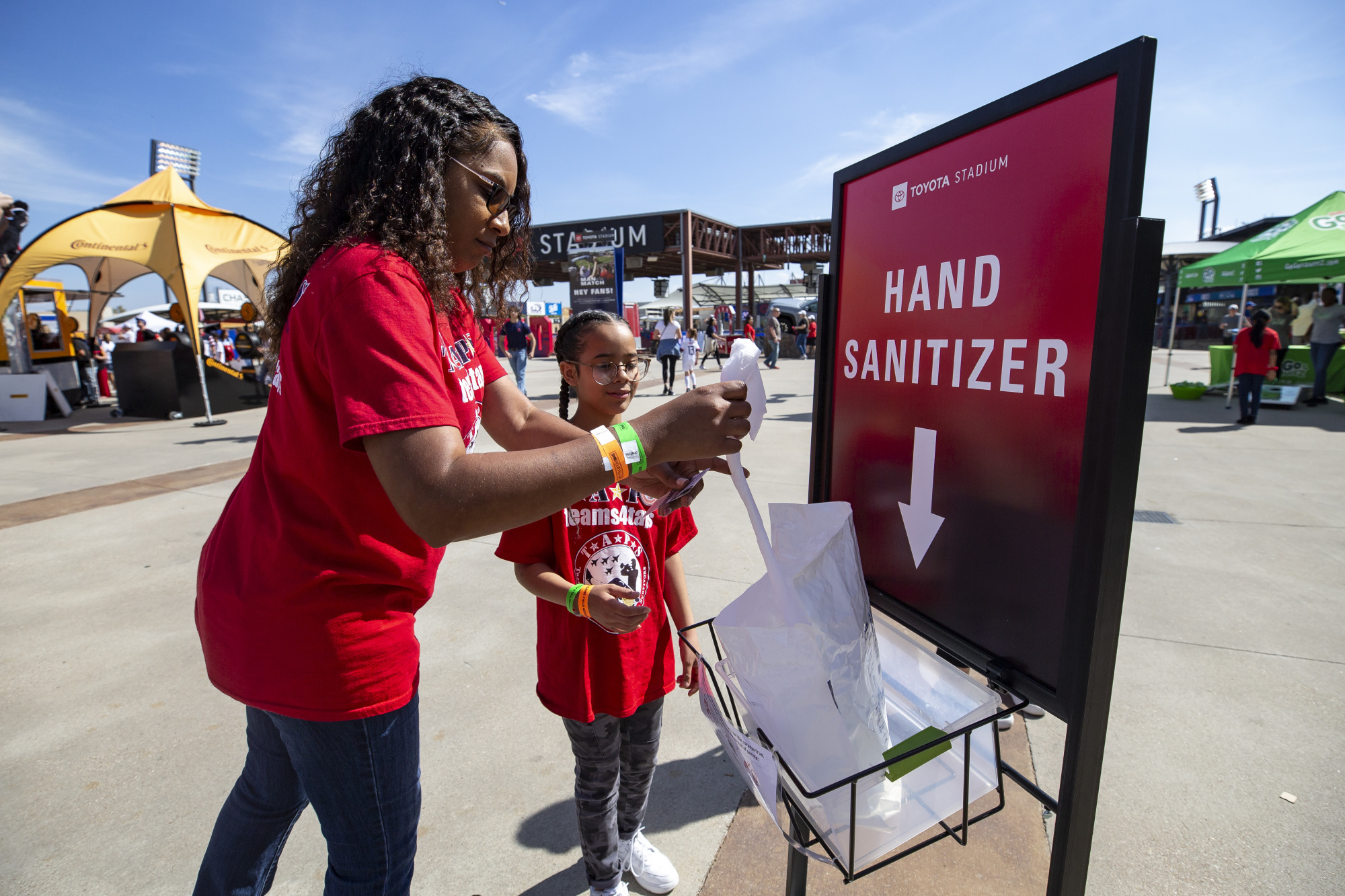 Fans pull sanitizing wipes from a dispenser outside Toyota Stadium before a SheBelieves Cup match between England and Spain on March 11 in Frisco, Texas. | AP
