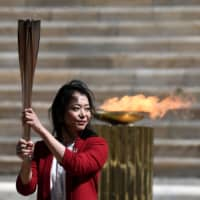 Former Japanese swimmer Naoko Imoto holds the Olympic torch during the olympic flame handover ceremony for the 2020 Tokyo Summer Olympics on March 19. | POOL / VIA REUTERS