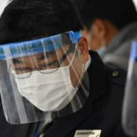 An quarantine officer wearing a face mask and shield works at a station at Narita International Airport in Chiba Prefecture on Monday. | AFP-JIJI