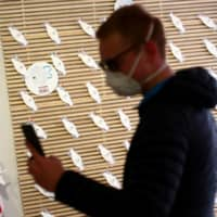 A man wearing a protective mask uses a smartphone in a shop for sanitary products in Vienna. | REUTERS