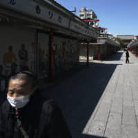 A person wearing a mask walks along the usually crowded shopping arcade near Sensoji Temple in Tokyo on April 23. | AP