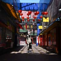 A man wearing a face mask stands in Yokohama's Chinatown area on April 9. | AFP-JIJI
