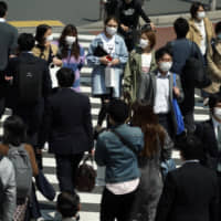 People with protective masks use a pedestrian crossing Thursday in Tokyo. | AP