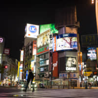 A pedestrian crosses a near-empty intersection in the Shibuya district of Tokyo on Sunday night. | BLOOMBERG
