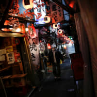 A man wearing a protective face mask, following the outbreak of the new coronavirus, walks past almost empty bars in an alley in Tokyo's Shinjuku Ward on Tuesday night. | REUTERS
