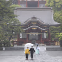 A handful of people wearing face masks to protect against the  new coronavirus walk in the rain at  Tsurugaoka Hachimangu shrine in Kamakura, Kanagawa Prefecture, on Monday. | AP