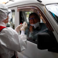 A medical worker conducts a simulation for drive-thru polymerase chain reaction (PCR) tests for the new coronavirus in Tokyo's Edogawa Ward on Wednesday. | REUTERS