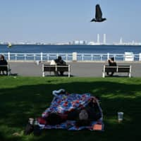 People rest during a sunny day at Yamashita Park in Yokohama on Saturday. | AFP-JIJI