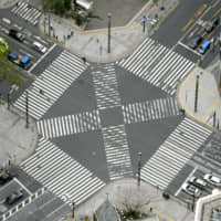 An aerial view shows a nearly empty pedestrian crossing in Tokyo's Ginza shopping district Sunday after Tokyo Gov. Yuriko Koike urged residents to stay indoors in a bid to keep the new coronavirus from spreading. | KYODO