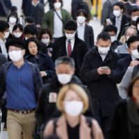 Train passengers wearing protective face masks following an outbreak of the new coronavirus walk to work the day before a state of emergency is expected to be imposed, at a rail station in Tokyo on Tuesday. | REUTERS