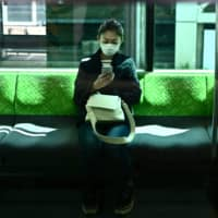 A woman uses her phone on a JR Yamanote Line train in Tokyo on Wednesday, the first day of a state of emergency covering Tokyo, Osaka and five prefectures. | AFP-JIJI