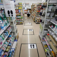 Footmarks indicate where customers should stand to keep distance from each other when in line amid the spread of the new coronavirus, at a Seven-Eleven convenience store in Tokyo on April 13. | REUTERS