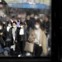 Correcting misinformation: Pedestrians wearing protective masks walk along a street in Tokyo's Shibuya district in March. | BLOOMBERG