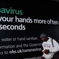 A man walks past coronavirus hand-washing advice on a billboard at Elephant and Castle in the borough of Southwark, which has among the highest number of COVID-19 coronavirus cases anywhere in the U.K., in London, England, on Monday. Official figures report that Southwark currently has 368 cases of COVID-19.   GETTY IMAGES / VIA KYODO