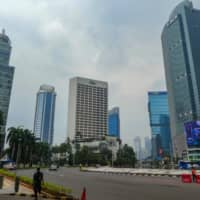 Motorists commute on a usually busy road in downtown Jakarta on Tuesday. | AFP-JIJI