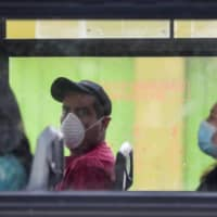 Commuters wear masks as they ride a bus to prevent the spread of the new coronavirus in Mexico City on Tuesday, March 31, 2020. | AP