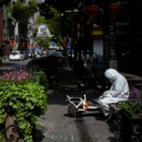 A woman wearing a hazmat suit uses her mobile phone along a street in Wuhan, in China's central Hubei province on Wednesday.  | AFP-JIJI