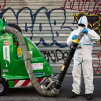 A Paris sidewalk is cleaned on Tuesday, the 15th day of a lockdown aimed at curbing the spread of COVID-19.   AFP-JIJI
