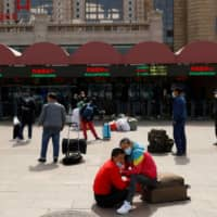 People wait outside Beijing Railway Station on Wednesday as the spread of COVID-19 continues.  | REUTERS