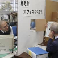 Tottori Prefectural Government officials talk through a cardboard partition on Tuesday. | KYODO