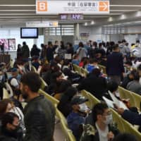 The Tokyo Regional Immigration Services Bureau in Minato Ward was congested on Wednesday as tourists unable to return home after the suspension of international flights due to COVID-19 added to the typical spring rush. | YOSHIAKI MIURA