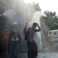 Boarding school students react as a worker sprays disinfectant on them before they travel back home by bus in Jombang, near Surabaya, East Java province, Indonesia, on Saturday.  | ANTARA FOTO / VIA REUTERS