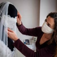 Clothing designer Friederike Jorzig adjusts a mannequin wearing a wedding dress with matching protective mask in her store Chiton in Berlin on Tuesday. | AFP-JIJI