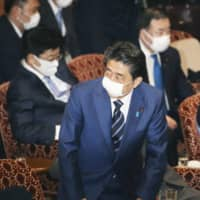 Prime Minister Shinzo Abe's decision to distribute two cloth masks to each household has drawn fire online, with many seeing it as out of touch with reality. | KYODO
