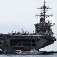 The USS Theodore Roosevelt enters a port in Da Nang, Vietnam, on March 5. | REUTERS