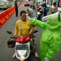 A medical officer checks a woman with a thermal scanner amid the COVID-19 outbreak in Tegal, Central Java Province, Indonesia on Tuesday.  | ANTARA FOTO / VIA REUTERS