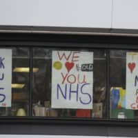 Signs in support of British National Health Service staff who are fighting the coronavirus outbreak are displayed at DLD College near St. Thomas' Hospital in London on Tuesday. | AP