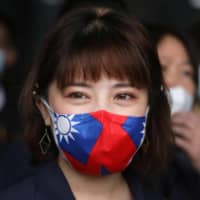 A factory worker wears a face mask with a Taiwanese flag design in Taoyuan, Taiwan, on Monday.  | REUTERS