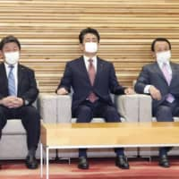 Prime Minister Shinzo Abe (center) and other Cabinet ministers wear face masks before a Cabinet meeting Friday at the Prime Minister's Office. | KYODO